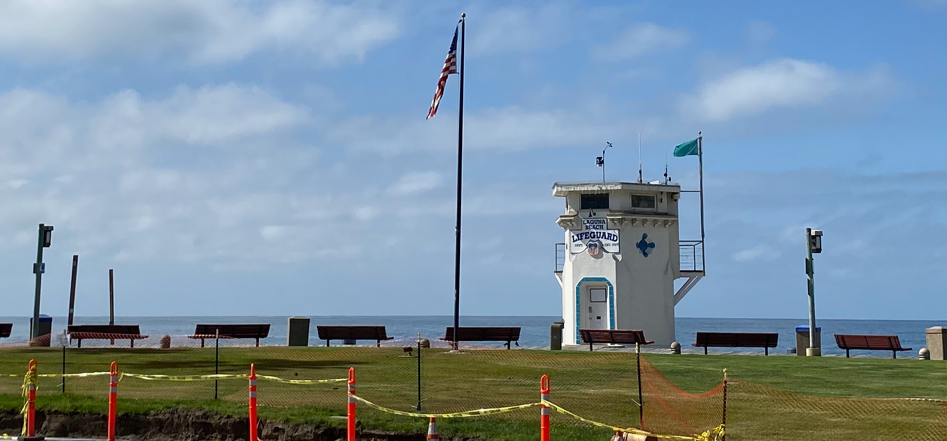 A cordoned off Main beach in Laguna Beach CA. Iconic lighthouse, American flag, empty benches, and caution tape.